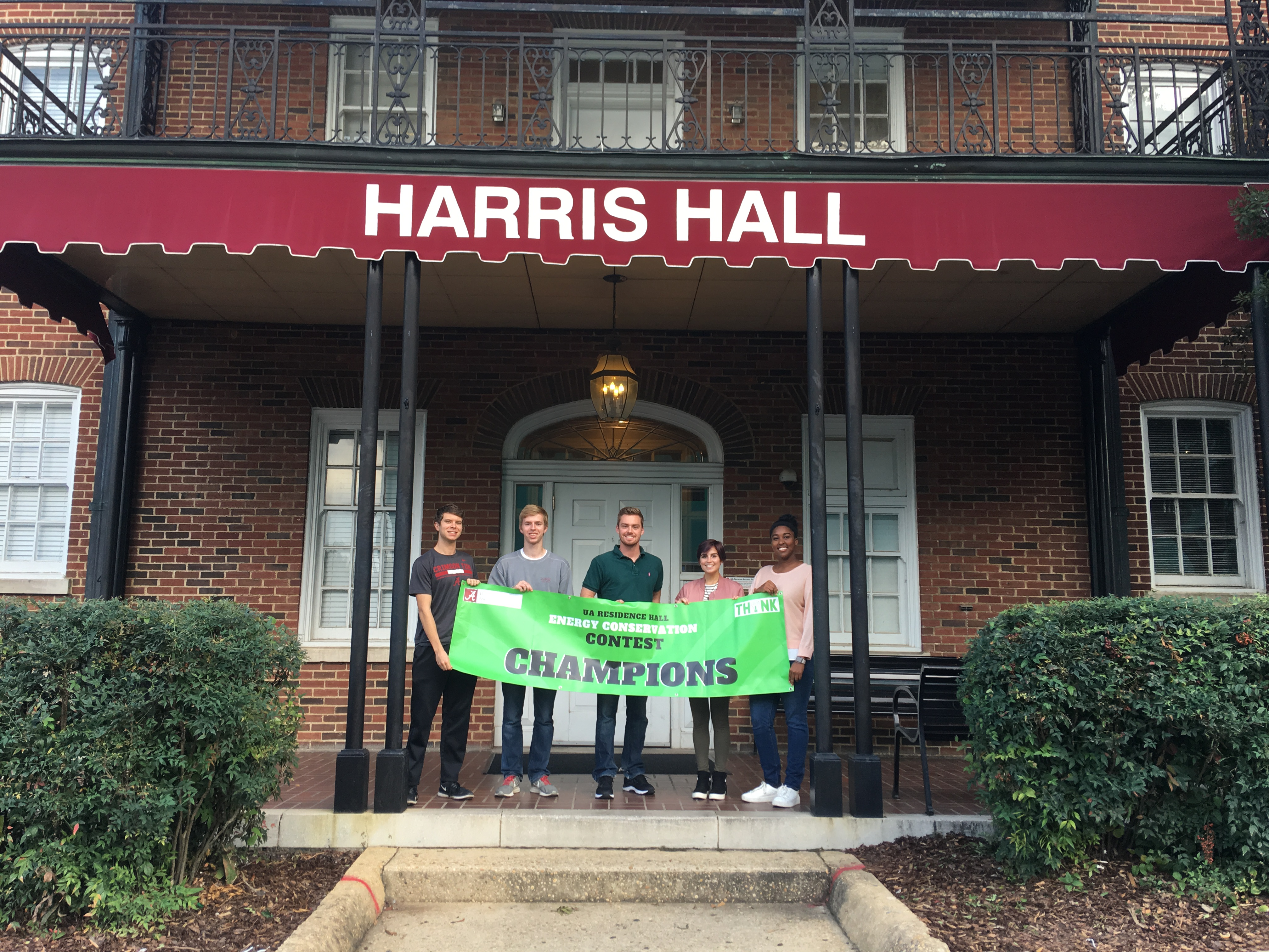 Students hold a banner outside Harris Hall as champions of the energy saving competition between the residence halls
